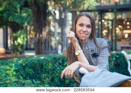 Stylish Young Happy Woman Sitting On The Bench Outside, Smiling At Camera, City Street With Storefro