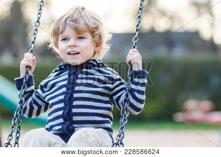 Portrait Of Toddler Boy Having Fun On Outdoor Playground. Happy Active Little Kid Child Playing, Swi