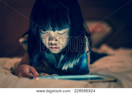 Kid Using Tablet For Gaming And Online Learning While Lying On The Bed, In Dim Light Bedroom Backgro