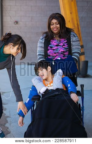 Two Caregivers Helping Take Care Of Disabled Eleven Year Old Boy In Wheelchair. Biracial, Asian Cauc