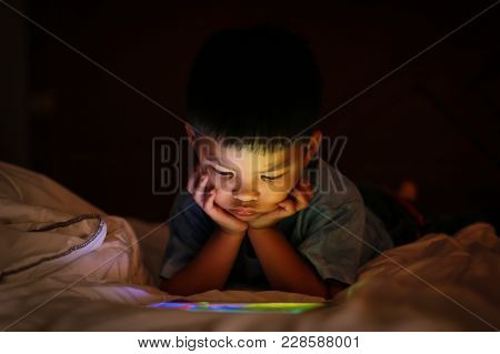 Little Asian Kid Alone Watching Tablet Device, Lying On White Duvet Bed With Chin On Hands, In Backg