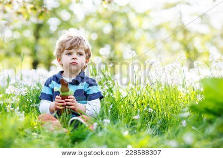 Cute Little Kid Boy With Easter Bunny Ears Celebrating Traditional Feast. Happy Child Eating Chocola