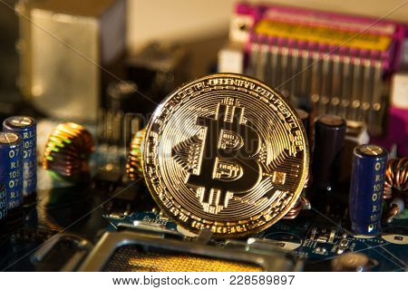 Gold Coin With A Gold Bit Of Bitcoin On A Background Of Microcircuits And Computer Spare Parts
