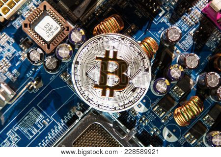 Silver Coin With A Gold Bit Of Bitcoin On A Background Of Microcircuits And Computer Spare Parts