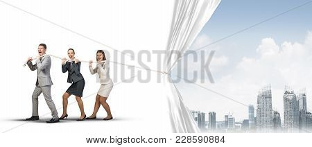 Three Businesspeople Pulling White Blank Fabric With Rope