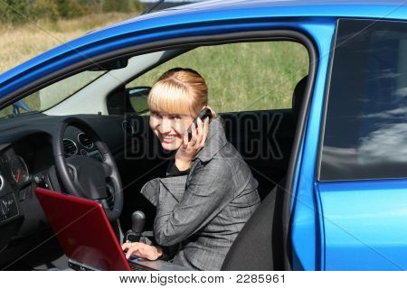 Young Blond Woman With Red Notebook In A Blue Car. She Is Smiling