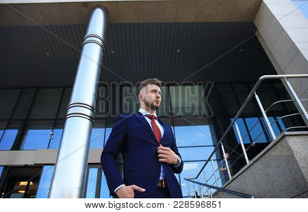 Portrait Of A Handsome Businessman In A Suit Standing Outside A City Building