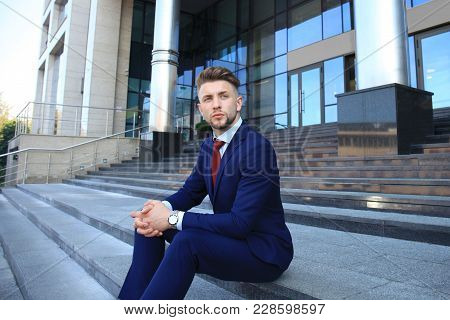 Handsome Male Business Executive Sitting On Stairs Outside A Building