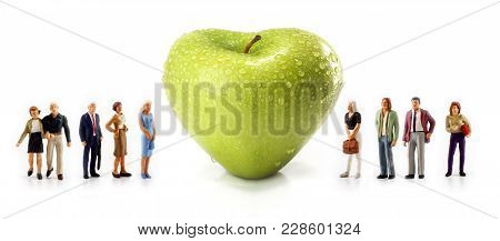 Miniature People - A Group Of People Pose Next To A Green Heart-shaped Apple Isolated On A White Bac