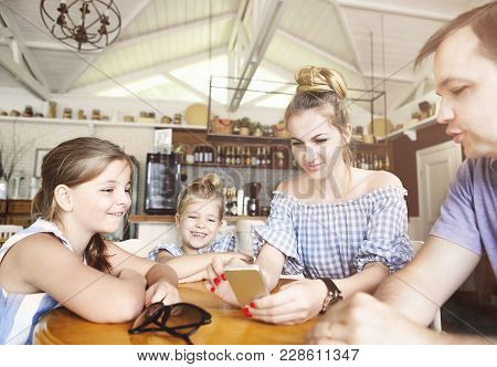 Happy Family With Two Daughters Having Dinner And Using Smartphone At Restaurant. Family, Parenthood