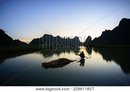 Sunset Landscape With Fisherman Fishing On Lake And Mountain In Cao Bang, Vietnam