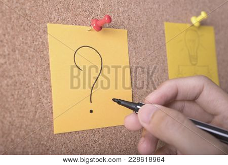 hand writing question mark on sticky note or post is on cork bulletin billboard. poster