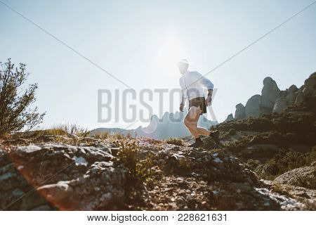 Professional Trail Runner, Ultra Distance Athlete Runs Through Rocky Terrain High On Mountain Path O