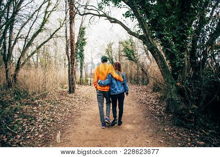 Young And Cute Couple Of Hipsters In Love Walk Through Forest Or National Park, Enjoy Time Spent On