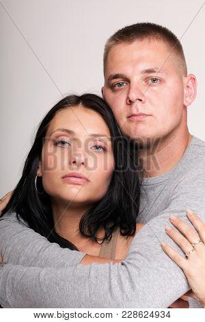 Beautiful Pensive Man And Woman Stand Near Gray Wal