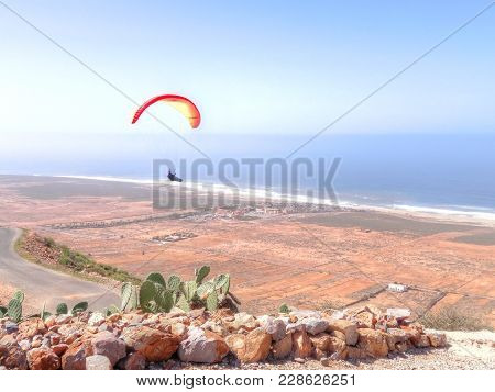 View From The Top Of A Mountain Or Sand Dune Across Rocks And A Road Of A Paraglider Flying Over An
