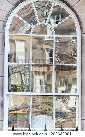 Old Window With Non-uniform Reflections In Glass