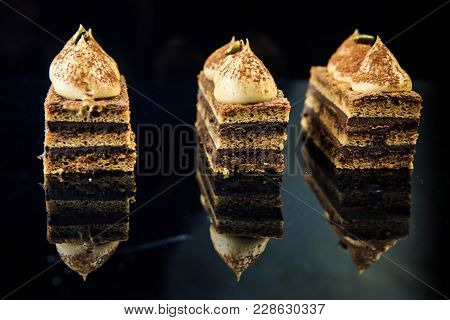 Delicious Opera Cake On Mirror Background