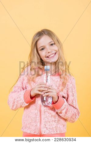 Happy Child With Drinking Water. Girl Smile With Water Bottle On Orange Background. Drink Healthy Wa