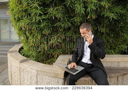 Male Manager Speaking By Smartphone Outdoors And Working With Laptop In  . Concept Of Modern Technol