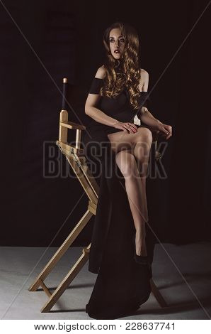 An Attractive Stylish Young Woman In A Long Black Dress Sits On A Chair In A Dark Room. Studio Photo