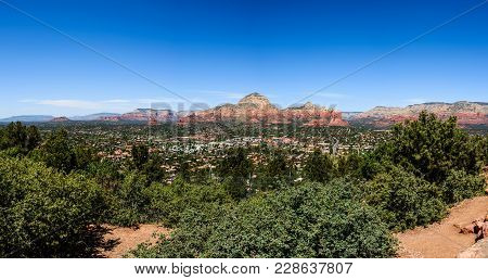 Panoramic View Of Sedona City In Arizona, Usa. Green Plants On The Foreground.