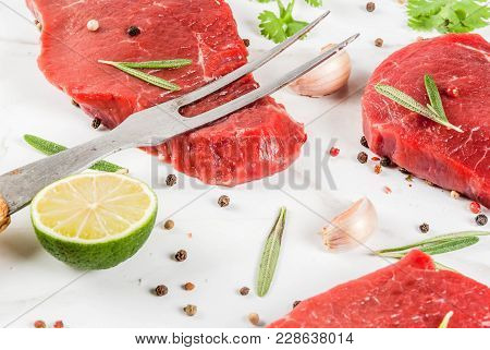 Fresh Raw Meat. Beef Tenderloin, Steaks, On A White Marble Table. With Olive Oil, Spices For Cooking