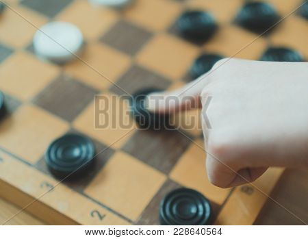Child Playing Checkers Board Game. Close-up View.