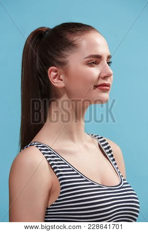 Beautiful Female Three-quarters Portrait. Isolated On Blue Studio Backgroud. The Young Emotional Hap
