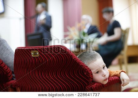 The Child Is A Spectator At A Concert Which Is Boring. Uninteresting View