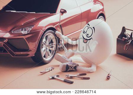 Funny Egg Car Mechanic Repair The Wheel. Vintage Instagram Stylization.