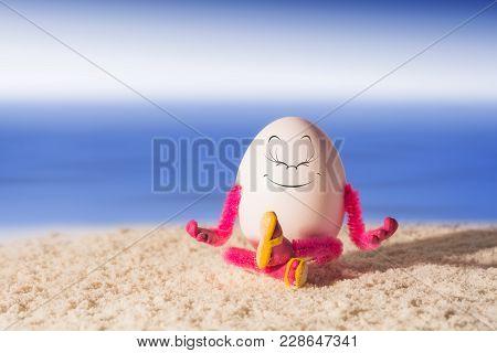 Funny Egg Girl Doing Yoga And Meditating On A Beach Near The Sea. Healthy Concept.