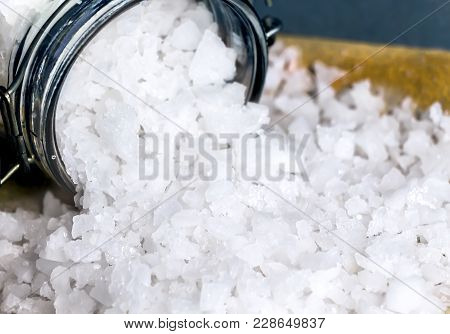 White Crystals Sea Salt In Glass Bottles Isolated On Table Background.