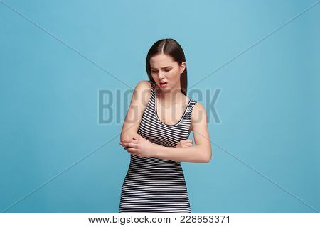 Elbow Ache Concept. The Sad Crying Woman With Elbow Ache Or Pain On Trendy Blue Studio Background. F