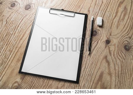 Clipboard With Blank Letterhead, Pencil And Eraser On Wooden Table Background. Blank Stationery Temp