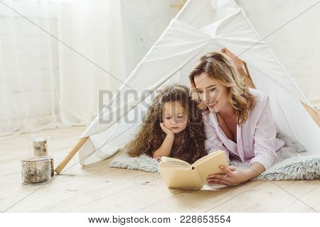 Happy Mother And Daughter Reading Book Together In Kid Wigwam