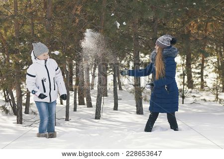 Two Teenage Girls In Warm Clothes Playing Snowballs Between The Trees In The Winter, Youth Fashion