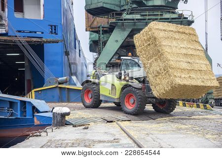 Telescopic Handler Loading Bales In A Ship. Day View. Work In Port.