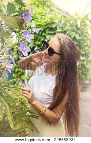 Woman Sniffing A Tropical Flower In The Garden