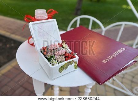 Close Up Little White Wedding Table With Box With Flowers And Registry Book On It Standing Outdoors