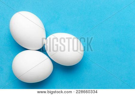 White Chicken Eggs On Blue Background, Close Up.