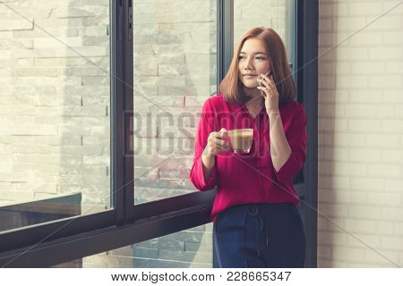 Young Beautiful Asian Woman Standing By A Large Window Using Her Phone And Holding A Cup Of Coffee,