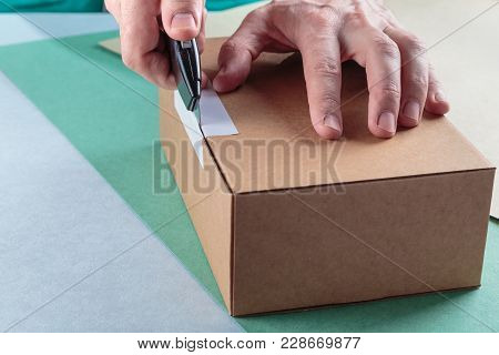 unboxing the parcels Packed in a cardboard box with a utility knife