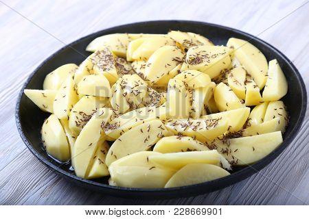 Crude Potato With Caraway Seeds. Potato On Frying Pan