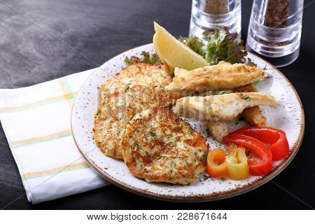 Fried Fish With Zuccini Pancakes And Fresh Vegetables