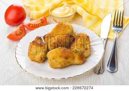 Fried Chicken Winglets In Breading In Plate, Tomatoes, Mayonnaise In Bowl, Fork And Knife On Wooden