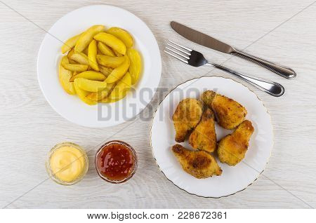 Fried Chicken Winglets In Breading, Fried Potato In Plates, Mayonnaise, Ketchup, Fork And Knife On W
