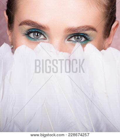 Face Of Young Beautiful Woman Closed With White Feathers. Professional Eye Makeup