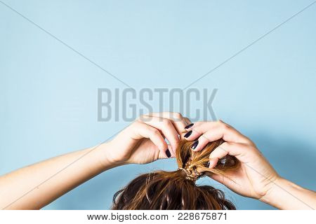 The woman straightens the disheveled bun on her head with her hands with a black manicure. Dark hair