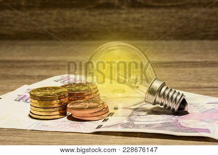 Lit European Bulb Placed On Czech Money